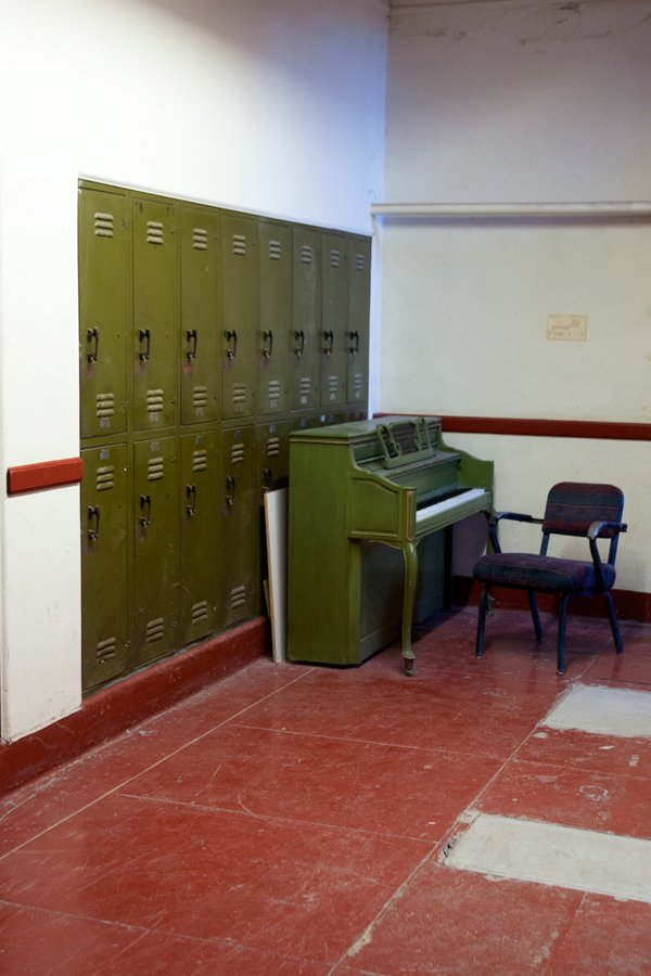 Lockers and a piano gather dust in the basement of the old Jerome High School in Jerome, Arizona, one of the biggest in the country during the town's mining boom. In recent years, the classrooms became occupied by artists who welcome tourists to their open studios. (Jain Lemos, Jerome, AZ; 2014.)